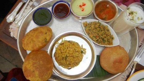 India - Il primo pasto della giornata consiste in patate arrosto al rosmarino, tofu, lenticchie, salsiccia vegetariana e peperoncino con banana abbrustolita.